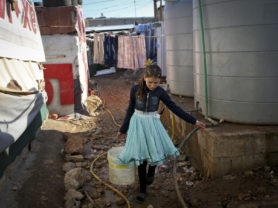 A daughter from the Ayyash family brings back water from a neighbor's tank, at an IS near Zahle, Lebanon, January 13, 2016. The Ayyash family has seven children, and they get the water from the neighbor's tank. Each tent should have a tank, but because they are still new in the camp, they still did not get theirs. The eldest girls fill the water in the bucket from the neighbors and walk with it to their tent. They heat the water on the heater. They take a shower each 10 days as they are afraid of getting sick due to the cold. (Photo Credit/Tara Todras-Whitehill for UNICEF)