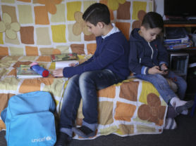 Syrian Mohamad Fakhoury, left, sits with his brother as he prepares his school work at his home in Beirut, Lebanon, January 15, 2016. (Photo Credit/Tara Todras-Whitehill for UNICEF)