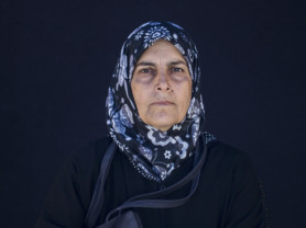 Fouda Al Bedwe, 67, from Homs, Syria, poses for a portrait in the Kara Tepe camp in Lesbos, Greece, Sept. 29, 2016. (Photo credit, Tara Todras-Whitehill/ Vignette Interactive for the IRC) Fouda- I was living happily with my children. I have many sons and daughters. The war came and suffering came with it. We got lost. I left with my son. My children are in different places. We came here without expecting this -- exhaustion and suffering. We've been suffering for five years. My son and his kids, me and my husband, we all became ill. All of this is because of the war. May God have mercy on us. We wish that God would help us to get to a safe country so that I, my son and his kids may live in stability. My dream was to see each one of my kids living in a house and to educate their children. My grandchildren left school. We left because of war. We suffered and we've been suffering for five years. My hope now is to settle in a safe country, me and my son.